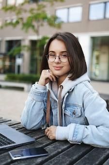 교육, 경력 기회 개념. 공원, 캠퍼스 야외에서 공부하는 매력적인 스마트 여성 학생, 노트북 및 스마트 폰으로 벤치에 앉아 카메라를 찾고, 프로젝트 준비, 코딩.