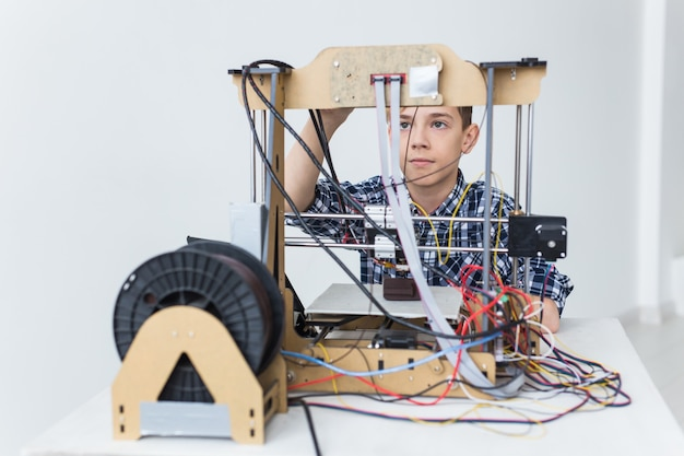 Education, children, technology concept - teen boy is printing on 3d printer.