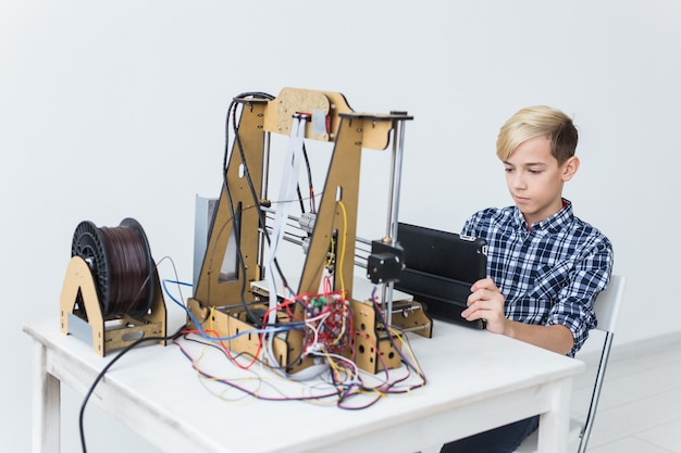 Education, children, technology concept. teen boy is printing on 3d printer.