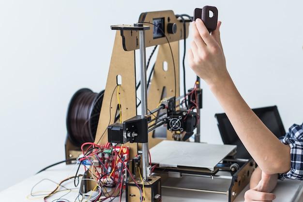 教育、子供、技術の概念-10代の少年は3dプリンターで印刷しています。