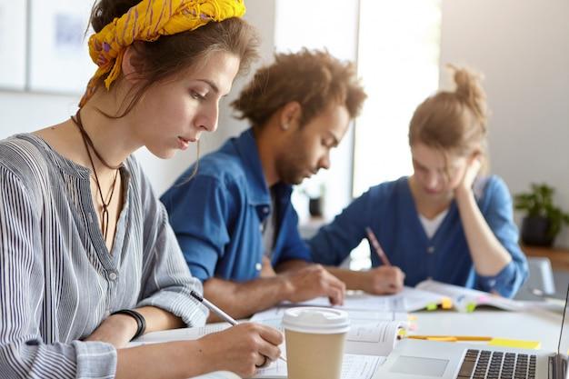 教育、大学および人々の概念。勉強のためにラップトップコンピューターを使用して鉛筆で書くコピーブックで真剣な表情を見て一緒に作業しているフレンドリーな学生のチーム