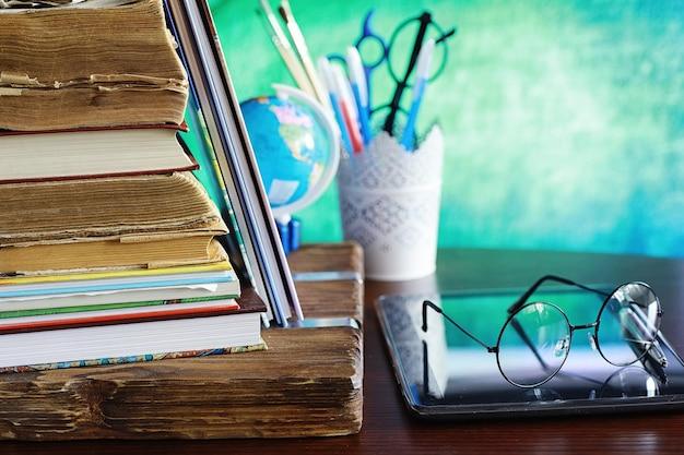 Концепция образования. стопка учебников и книга на столе с очками и компьютером. яблоко школьного завтрака и домашнее задание.