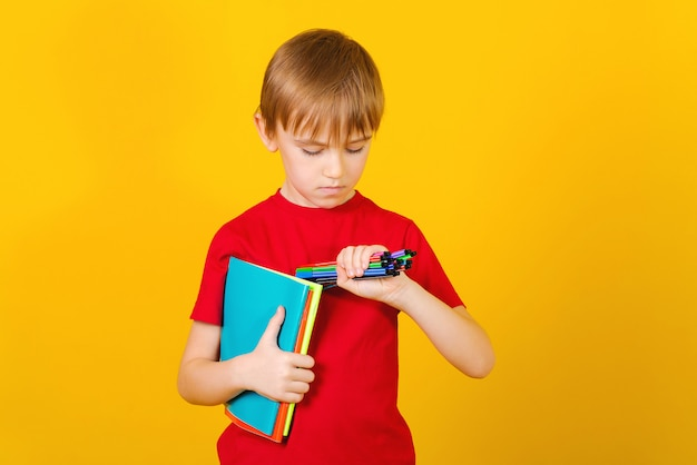 Education concept. cute boy holds school supplies. kid with a stationery on a yellow background.