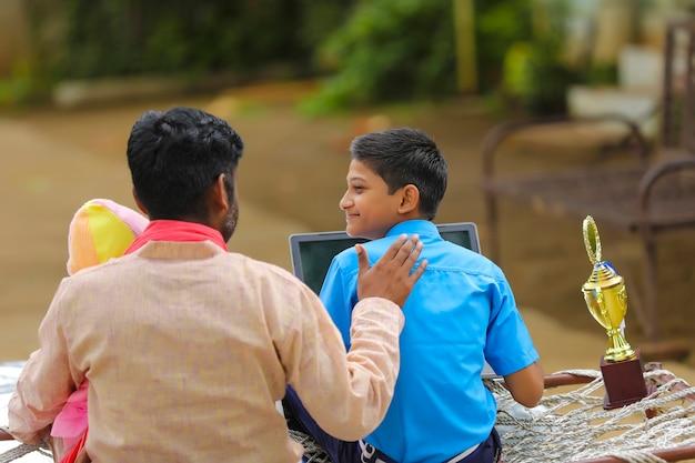 교육 개념:노트북을 사용하고 아버지에게 정보를 제공하는 귀여운 인도 학교 소년.