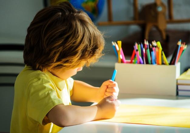 教育の概念。小学校。子供の男の子は宿題を書きます。小学校。