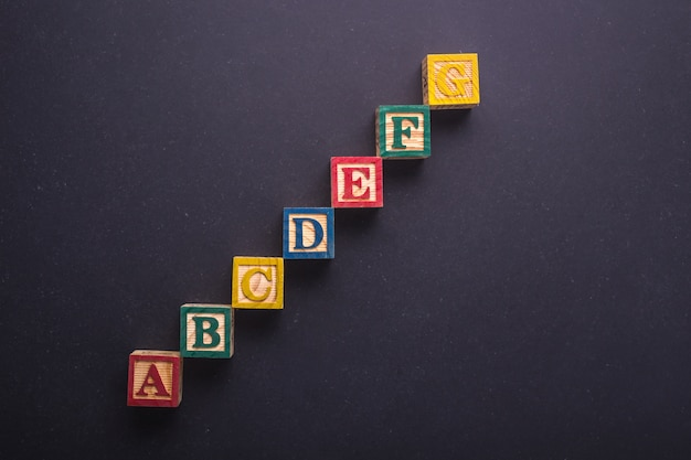 Education concept. a-g colorful wood alphabet blocks on black stone board background