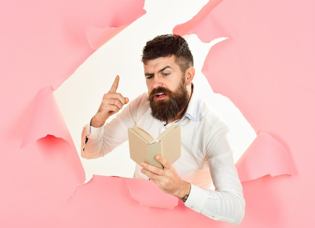 Education concept handsome bearded man from hole in wall raised his finger up scientist professor