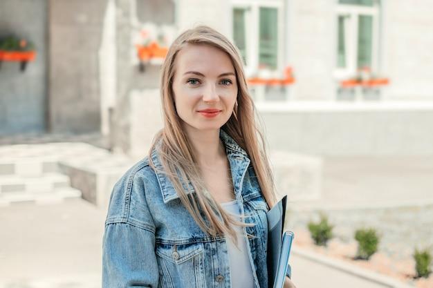 Концепция образования. счастливая студентка держит в руках папки, тетради, книги, улыбается, смотрит в камеру на фоне здания современного университета