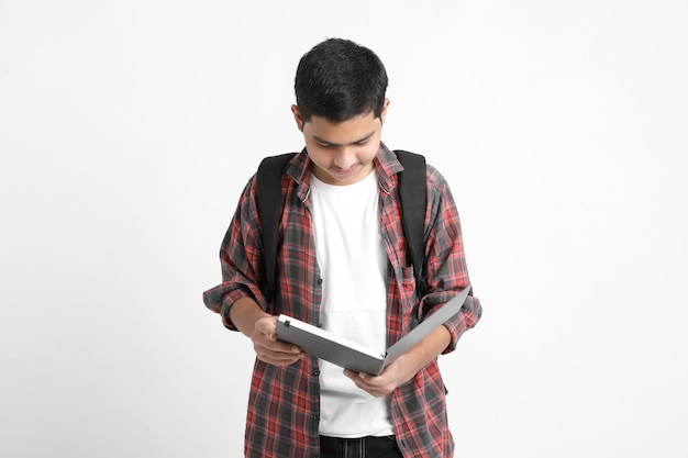 Education concept : indian college student holding bag and reading book on white background