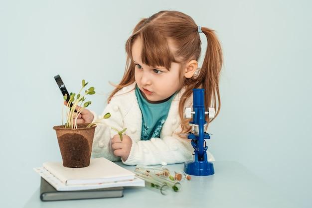 教育の概念。小さな女の赤ちゃんが実験室の顕微鏡を見てください。