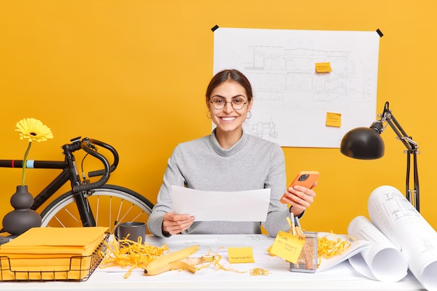 Education concept. positive female student of architect faculty glad to finish home task holds paper with drawings and modern smartphone poses in coworking space alone works on construction project