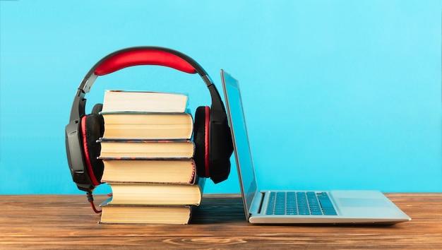 Концепция образования. стопка книг и ноутбука, наушников - копией пространства.