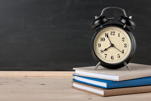 黒板の背景に本と目覚まし時計と教育の概念