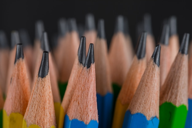 Education concept with pencils on dark close-up.