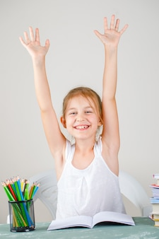 Education concept with school supplies side view. little girl smiling and raising hands.