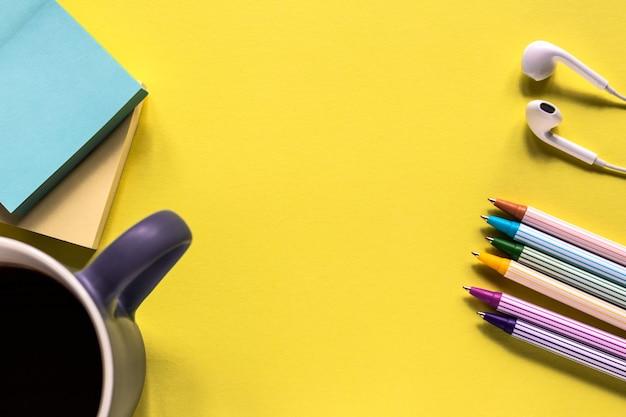 付箋、ペン、ハンドスプリング、黄色の背景にコーヒーのマグカップの教育コンセプト
