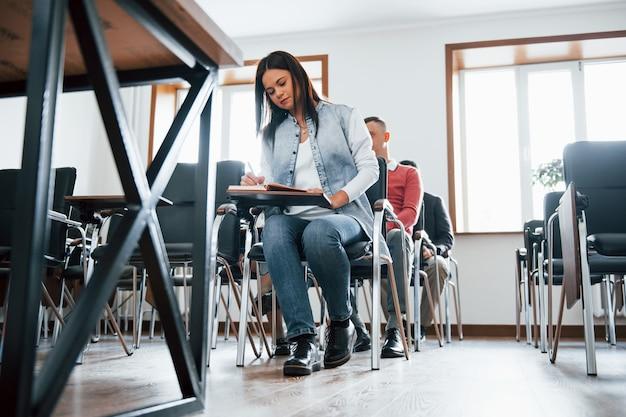 Concezione dell'istruzione. gruppo di persone alla conferenza di lavoro in aula moderna durante il giorno