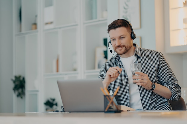 Education and e learning concept. satisfied busy man focused at laptop display watches educational webinar listens audio course via headphones sits at desktop enjoys virtual studying with tutor