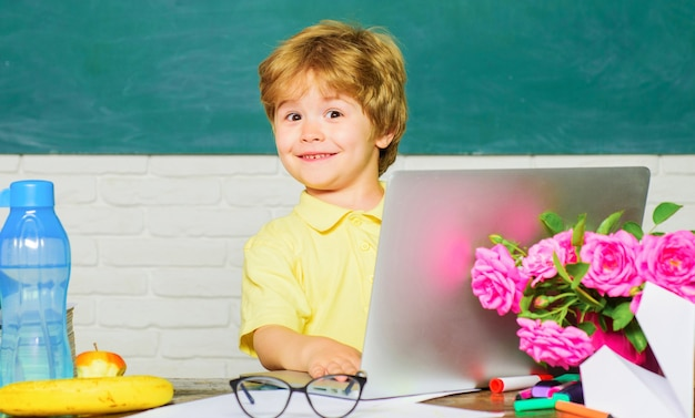 Education and e-learning. little schoolboy with laptop in classroom. kid at school.