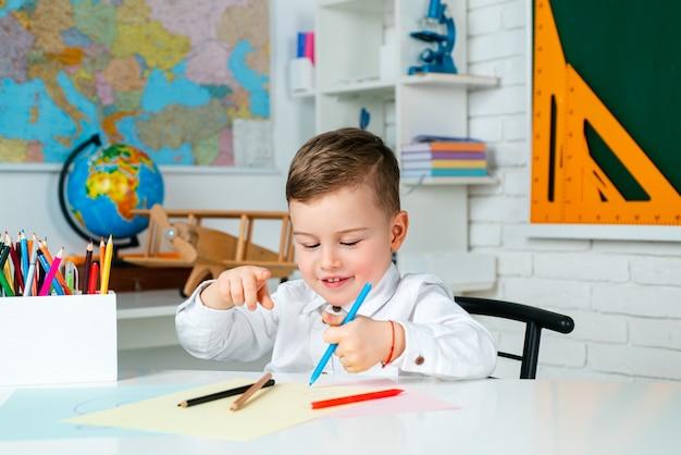 教育、小学校、子供たちの学習の概念。ペンとノートを持った学校の子供たちが教室でテストを書いています。学校の教室の子供。学校のコンセプト。