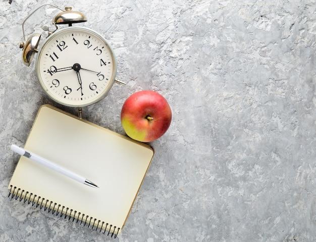 Education equipment. alarm clock, notepad,, apple, pen,. top view, flat lay style