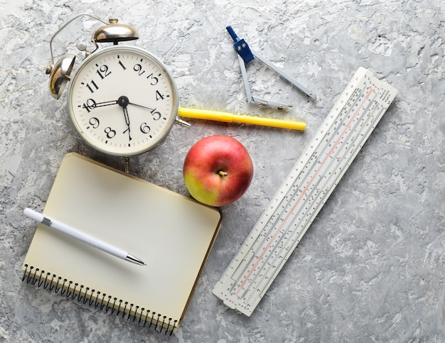 Education equipment. alarm clock, notepad, ruler, apple, pen, compasses. top view, flat lay style