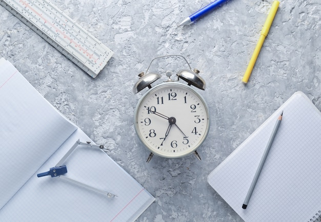 Education equipment. alarm clock, notepad, ruler, pen, compasses. top view, flat lay style