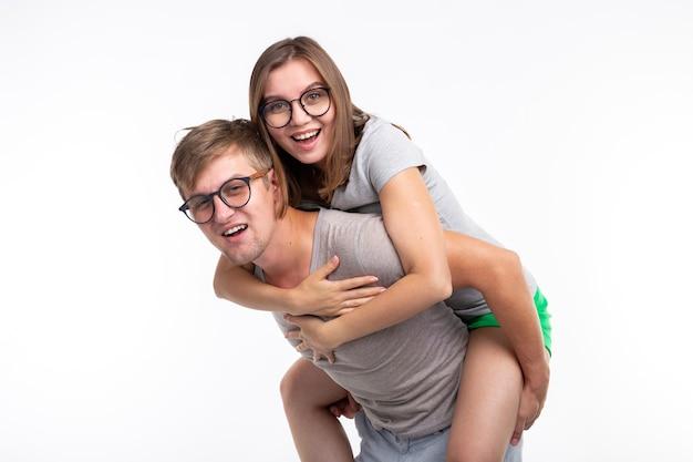 교육, 재미있는 사람과 농담 개념-젊은 여자가 남자의 등에 뛰어 들었습니다. 그들은 행복하다