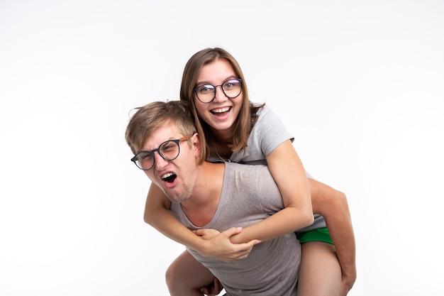 교육 재미있는 사람과 농담 개념. 한 젊은 여자가 남자의 등을 뛰고 그들은 행복하다