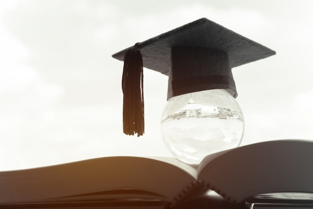Education in global, graduation cap on top crystal ball on textbook.
