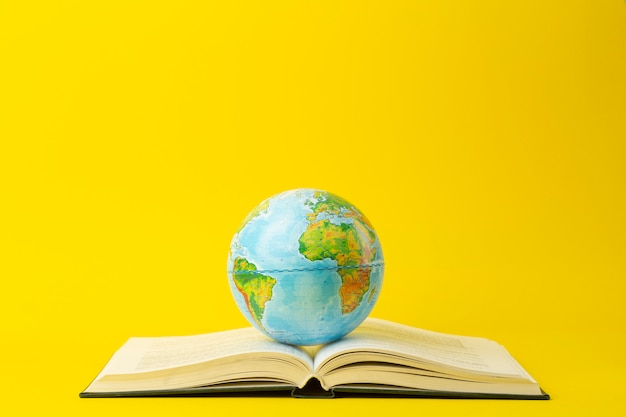 Education and globalism concept. globe on an open book on a table in a university class on a yellow background
