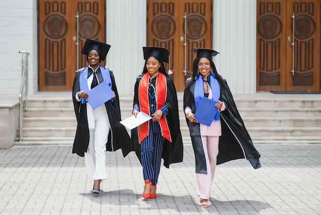 Концепция образования, выпуска и людей - группа счастливых международных аспирантов в минометных досках и бакалаврских халатах с дипломами