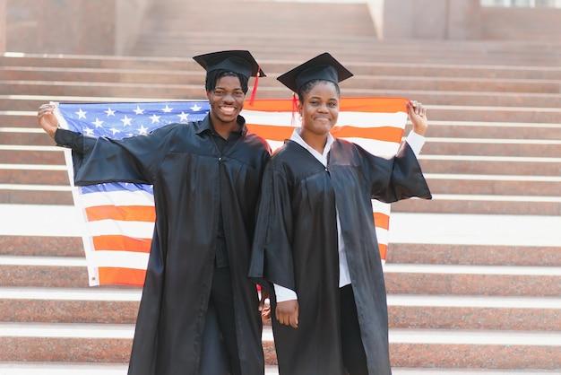 Концепция образования, выпуска и людей - счастливые иностранные студенты в минометных досках и бакалаврских халатах с американским флагом
