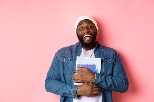 教育。ノートブックを持って、コースを勉強し、カメラに微笑んで、ピンクの背景の上に立ってビーニーで幸せなアフリカ系アメリカ人の男子学生