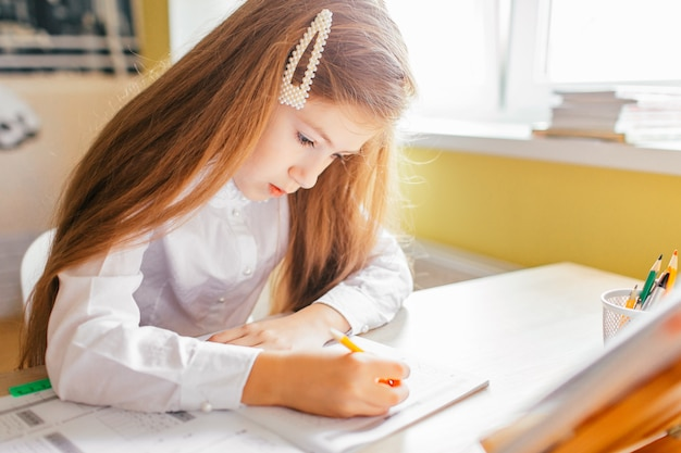 Education at home concept - cute little girl with long hair studying or completing home work on a table with pile of books and workbook
