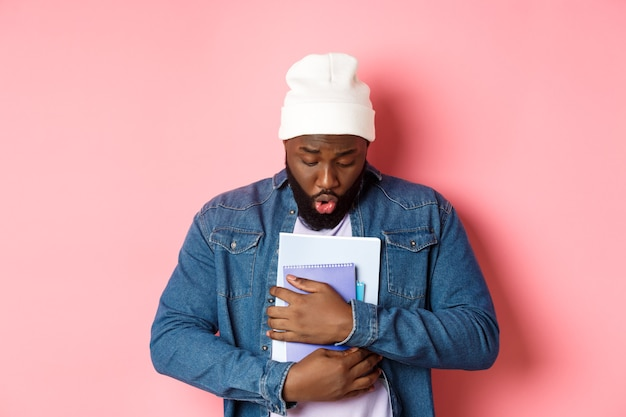 教育。ノートブックを持って見下ろし、床に何かを落とし、ピンクの背景の上に立っているアフリカ系アメリカ人のひげを生やした男性学生の画像