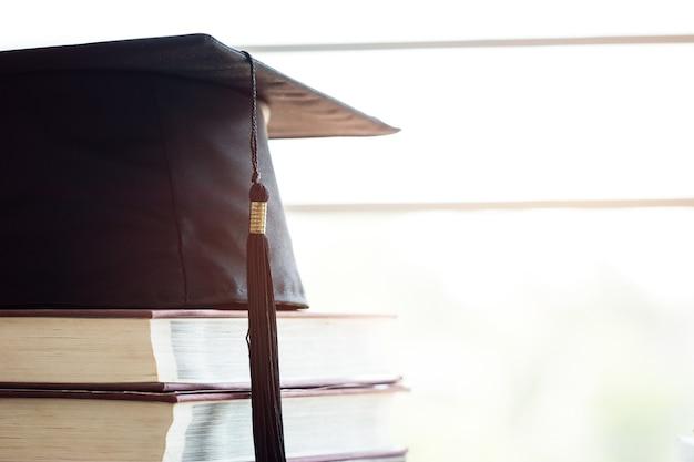 Образование, знания, обучение, обучение за рубежом, международные идеи. выпускной в шляпе на стопке учебников с литературой в библиотеке, альтернативное обучение во всем мире и снова в школу.