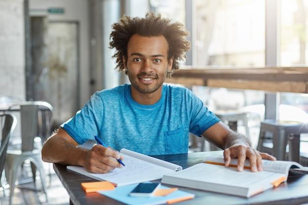Istruzione e conoscenza, persone e stile di vita. ritratto interno di allegro studente universitario dalla carnagione scura che fa compiti a casa in matematica, lavora presso la caffetteria, prendendo appunti dal libro di testo