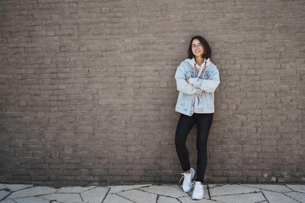 Концепция образования, образа жизни и современного поколения. уверенно счастливая молодая женщина в джинсовой куртке, очках, тощей кирпичной стене и улыбается, скрестив руки на груди уверенно, отправляя резюме найденную работу.