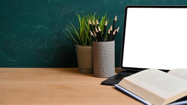 教育モックアップの概念。タブレットの空白の画面のモックアップ、鉛筆、植物、黒板の上の木製のテーブルの空きスペースで開いた本
