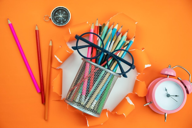 Education objects on orange ripped open paper background