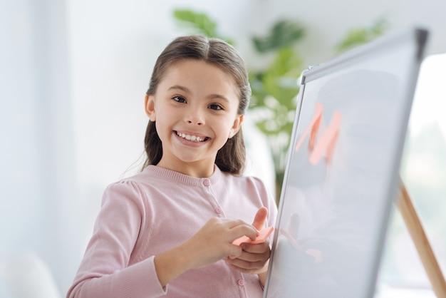 교육 프로젝트. 화이트 보드 근처에 서서 당신을 보면서 스티커 메모를 붙이는 귀여운 긍정적 인 좋은 소녀
