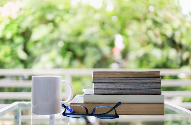 Education and relaxation concept. closeup of white  mug cup of hot coffee, reading glasses and books on glass table in green garden view