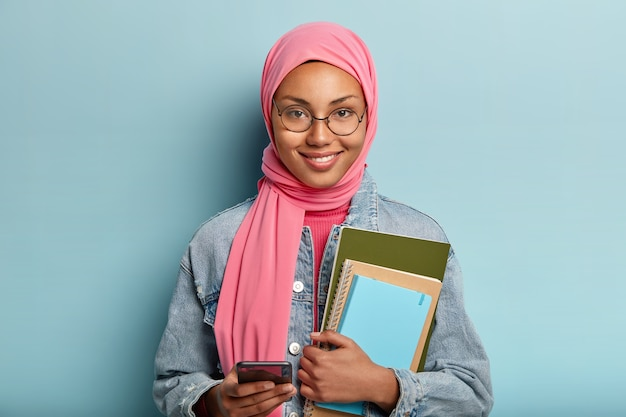 Education and religion concept. spiritual mixed race female student uses cell phone for surfng internet, holds necessary notebooks for writing, wears round spectacles and pink veil, stands indoor