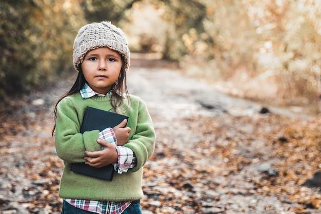 教育、学校、人々の概念。幸せな笑い小さな瞳孔の女の子を持って大きな重いバックパックを持ち上げてみてください