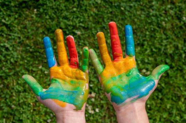 教育、学校、芸術、痛みを伴う概念-草の上に学校で塗られた手を見せている小さな学生の女の子