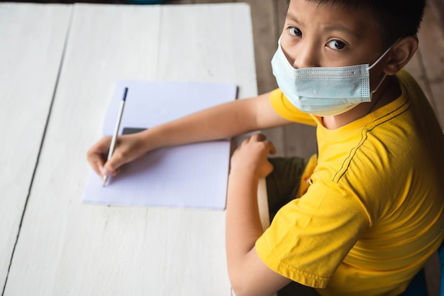 Education, school and pandemic concept - student boy wearing face protective medical mask