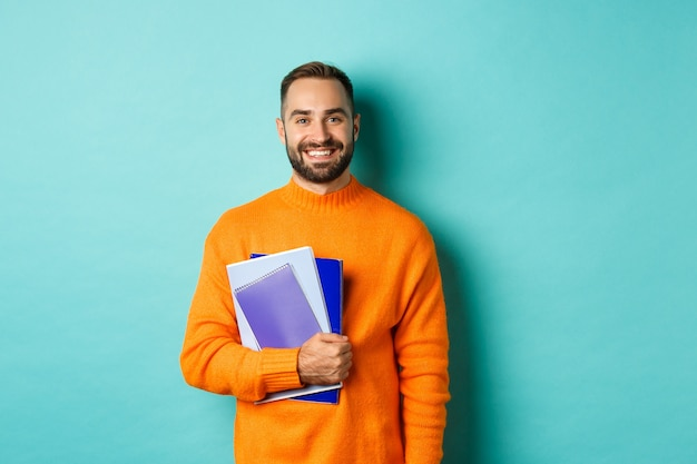 교육. 노트북을 들고 웃고, 코스를 진행하고, 가벼운 청록색 벽 위에 서있는 수염 난 남자를 웃고