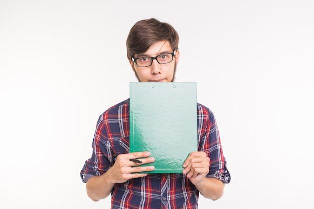 教育、学生、ビジネスマンの概念-ファイルと鉛筆を持つ若い男。男は恥ずかしがり屋で混乱しています