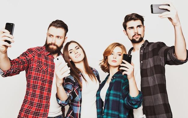 教育、技術、人々の概念:白い背景の上にスマートフォンで自分撮りをしている学生のグループ。特別なファッショナブルな調子。